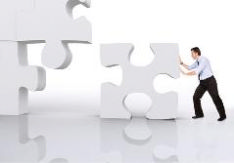 The image shows a man pushing the missing jigsaw piece into the last space in the jigsaw, reflecting the idea of the recruiter finding the perfect candidate for the job they have been advertising.